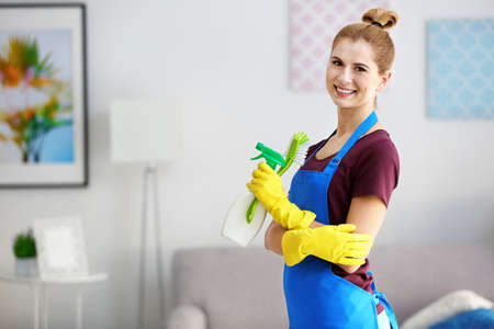 Pretty adult woman with cleaning supplies at home