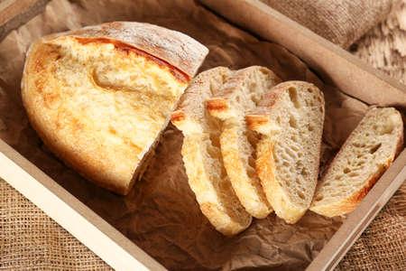 Sliced fresh bread in wooden box closeup