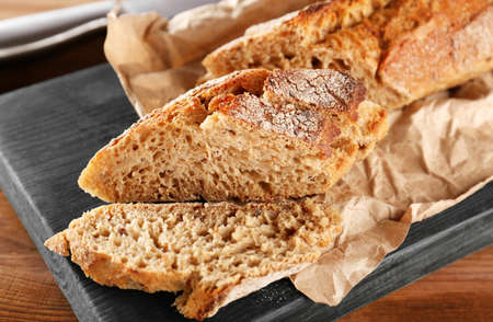 Sliced rye bread on wooden cutting board closeup