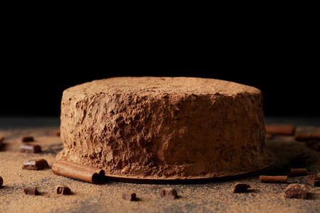 Tasty chocolate cake with cinnamon on black background