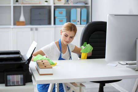 Pretty adult woman wiping table in office