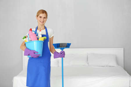 Pretty adult woman with cleaning supplies in bedroom