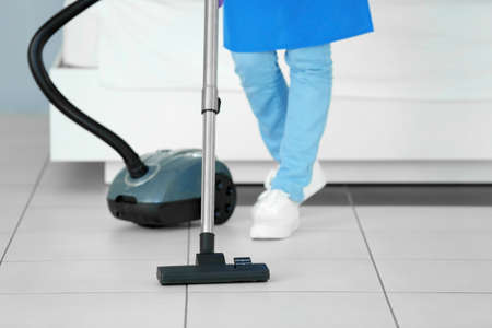 Close up view of woman hoovering floor with vacuum cleaner
