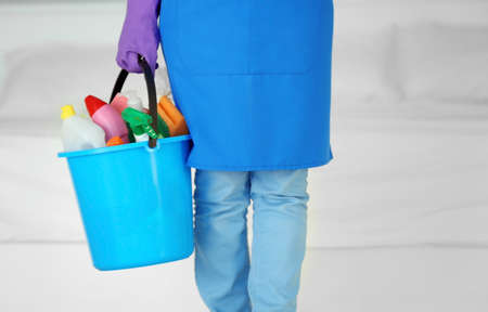 Close up view of woman with cleaning supplies at home