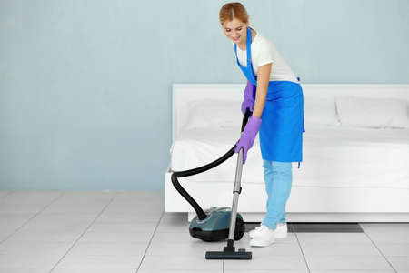 Pretty adult woman hoovering floor with vacuum cleaner