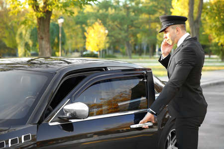 Young chauffeur speaking by cellphone near luxury car on the street Reklamní fotografie