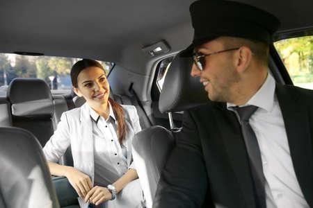 Businesswoman riding a car with chauffeur Reklamní fotografie - 97445528