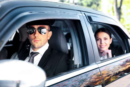 Businesswoman riding a car with chauffeur Reklamní fotografie - 97076634