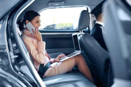 Geschäftsfrau, die durch Mobiltelefon spricht und ein Auto reitet