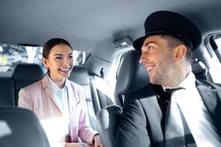 Businesswoman riding a car with chauffeur Reklamní fotografie - 97445810