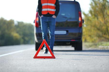 Red warning triangle on asphalt road. Tow truck worker near broken down car
