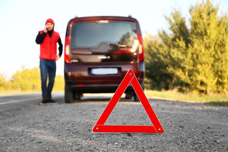 Red warning triangle on asphalt road. Driver near broken down car calling for help