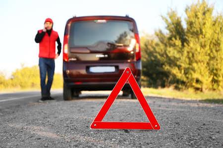 Triangolo rosso su strada asfaltata. Autista vicino alla macchina rotta per chiedere aiuto Archivio Fotografico - 97052445