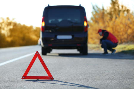 Red warning triangle on asphalt road. Driver near broken down car