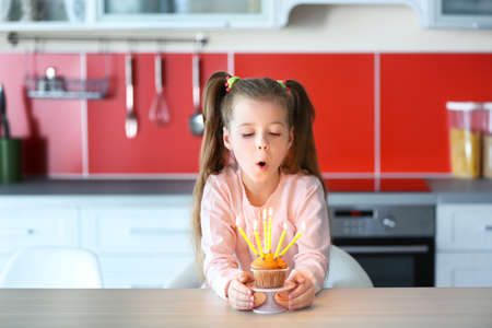 Cute little girl blowing out candles on birthday cake in kitchen Stock Photo