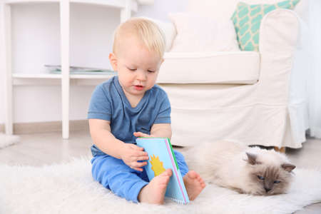 Cute little boy with fluffy cat on floor Stock Photo