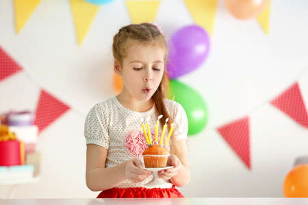 Cute little girl blowing out candles on birthday cake at home Stock Photo