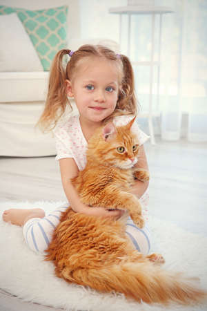 Cute little girl with red cat at home Stock Photo