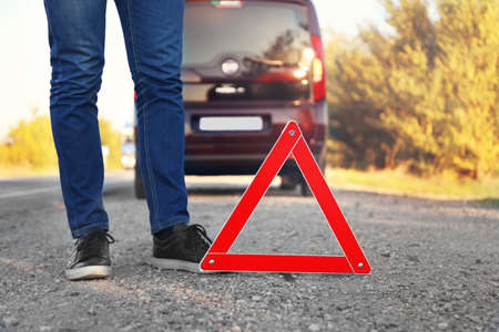 Legs of driver standing near red warning triangle on asphalt road. Emergency stop concept