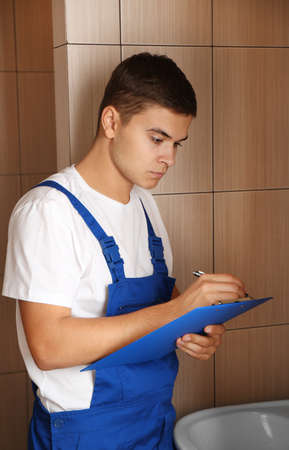 Young handsome plumber with clipboard indoors