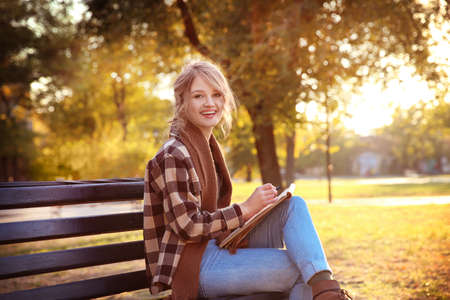 Young female artist drawing sketch while sitting on bench in beautiful park Stock Photo