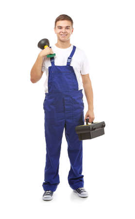 Young handsome plumber with tools on white background