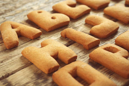Cookie alphabet on wooden background, closeup