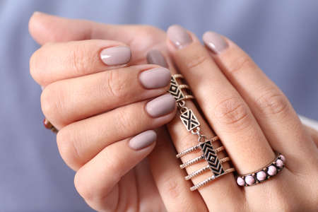 Close up view of female hands with beautiful manicure on blurred color background