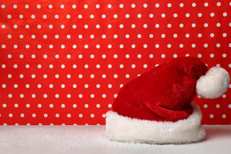 Santa Claus hat on red spotted background