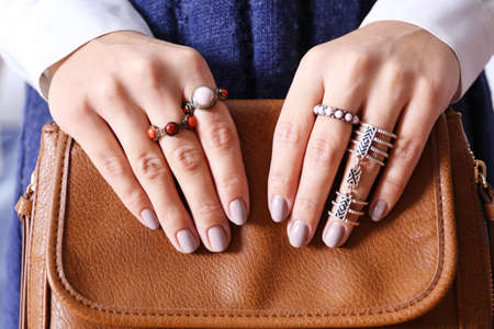 Close up view of female hands with beautiful manicure holding leather handbag