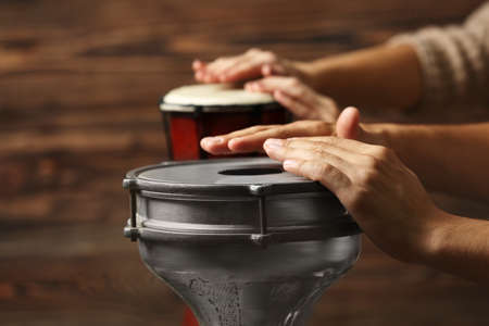Hands of man playing African drum on brown blurred background