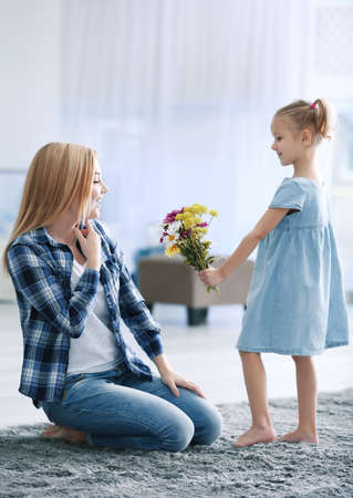 Little girl greeting her mother with flowers at home. Mother's day concept