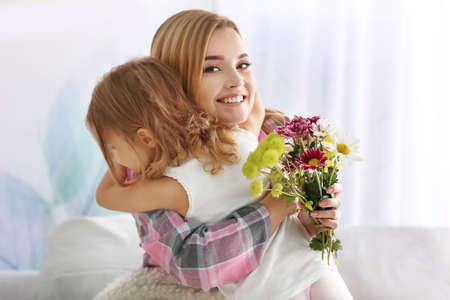 Beautiful young woman hugging her daughter at home. Mother's day concept