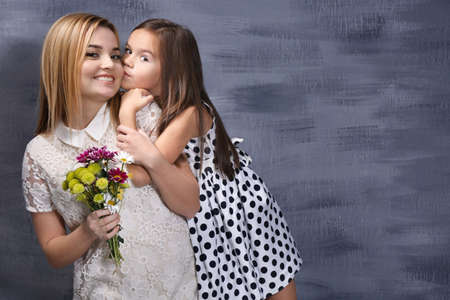 Beautiful young woman with bouquet and her daughter near color wall. Mothers day concept