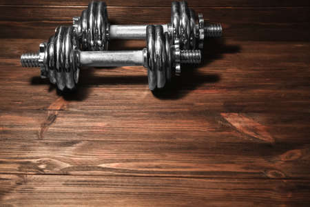 Metal collapsible dumbbells on wooden background