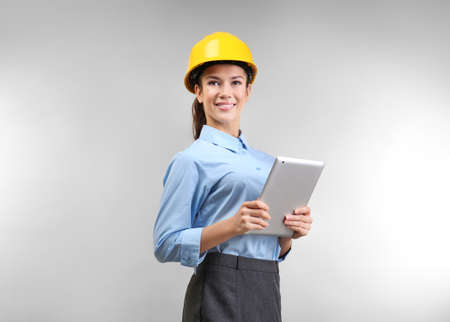 Confident young woman with hardhat and tablet computer, on light background