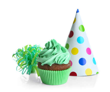 Tasty cupcake and party hat on white background