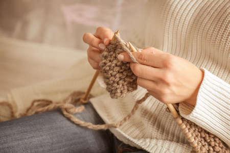 Closeup of woman knitting warm scarf