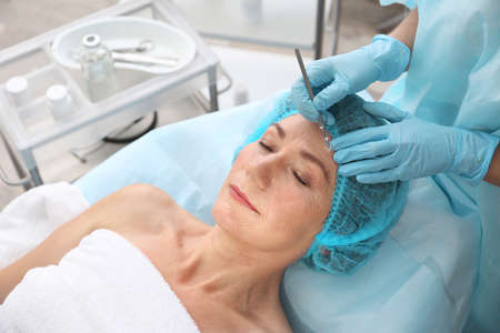 Surgeon operating female patient with scalpel at beauty salon