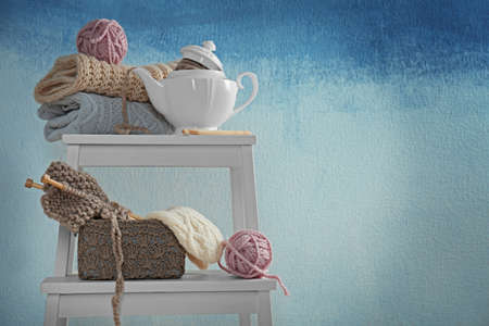 Knitwear, yarn and teapot on white little table Stock Photo