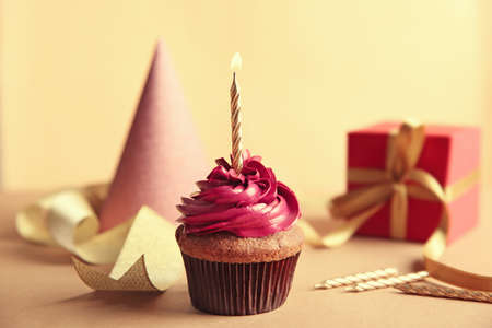 Birthday cupcake with gift box and party hat on light background