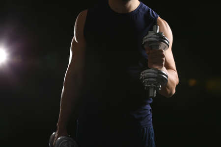 Sporty man doing exercises with dumbbells on black background, closeup