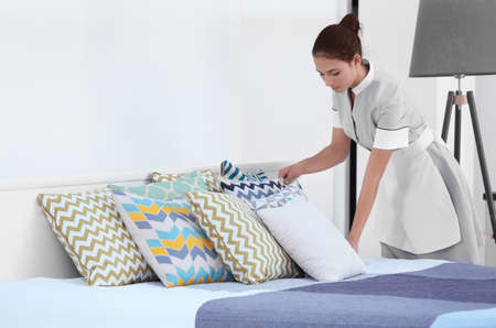 Female chambermaid making bed in hotel room Stock Photo