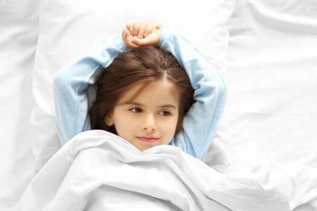 Funny little girl lying in bed at home Stock Photo
