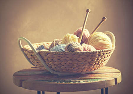 Knitting wool and needles in wicker basket Stock Photo