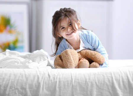 Funny little girl lying on bed with cuddly toy Stock Photo