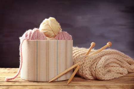 Balls of knitting yarn in box and needles on wooden table Stock Photo