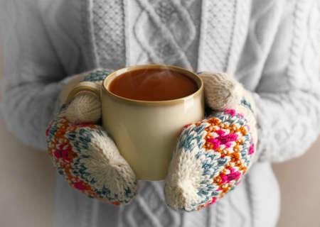 Manos femeninas en guantes sosteniendo una taza de café, primer plano