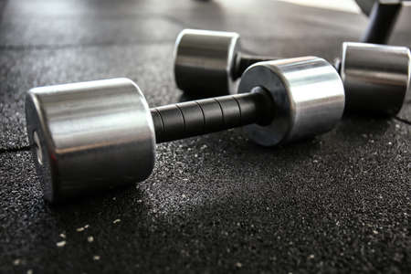 Pair of dumbbells on floor in gym, close up