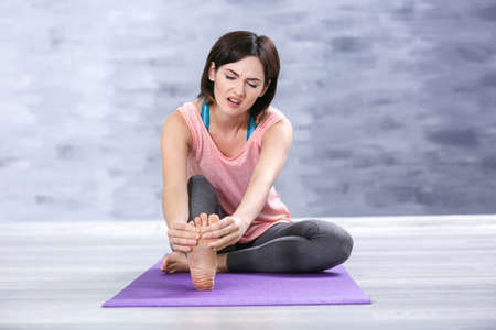 Beautiful young woman suffering from pain in foot while sitting on stretching mat indoors